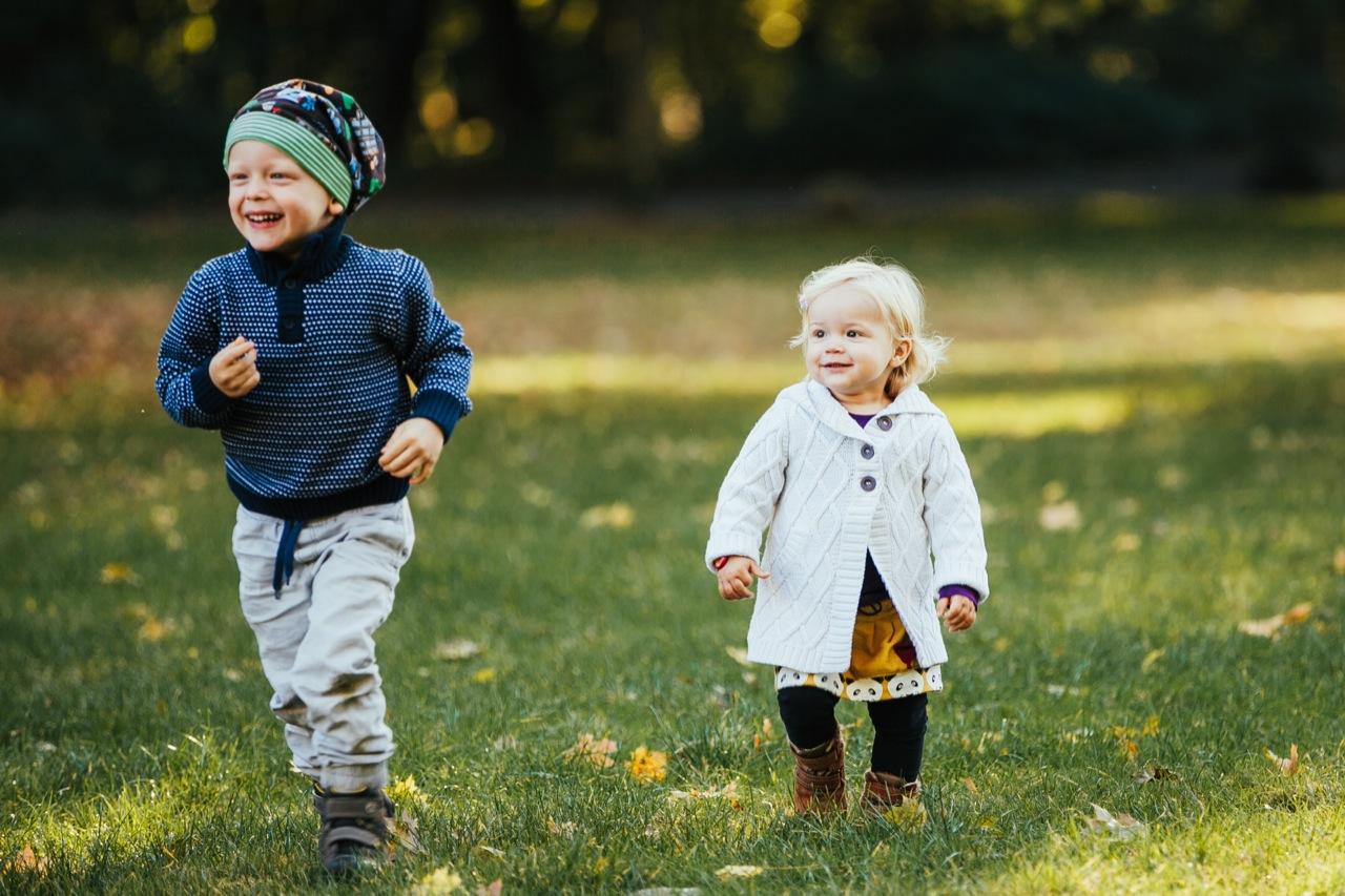 Bruder und Schwester laufen auf einer Wiese